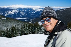Caucasian senior man skier in goggles posing on mountain.